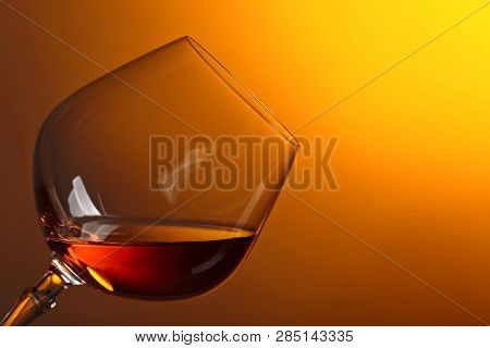 Snifter Of Brandy With Copy Space For Text On A Yellow Background.