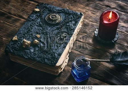 Ancient Magic Book, Ink Well And A Quill Pen On A Wooden Table Background. Spell Book.