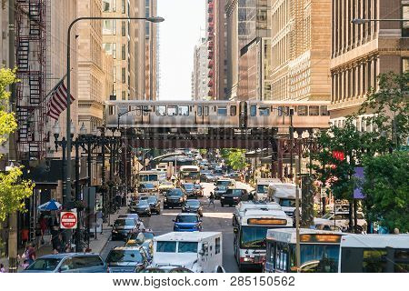 Traffic In Downtown Chicago With People, Train, Car And Bus