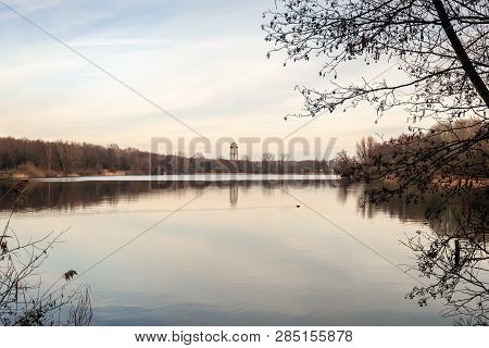 Look Through To A Dutch Lake Between The Branches Of An Alder Shrub With Bare Branches And Catkins.