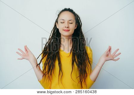 Calm Healthy Beautiful Girl With Dreadlocks And In A Yellow Bright Sweater Meditating For Stress Rel