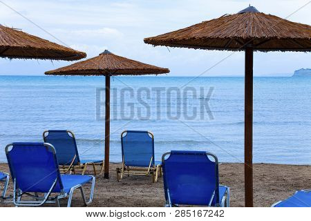 Beach At Sea With Canyon And Sandy Beach. Plastic Seats On The Sandy Beach. Holiday Concept With Bea