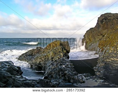 Boulder On The Seashore About Which Waves Are Broken. Sea Spray In The Sun. Stone In Algae. The Sea