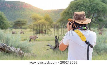 Young Asian Man Traveler And Photographer Taking Photo Of Wildlife Animal In African Safari. Wildlif