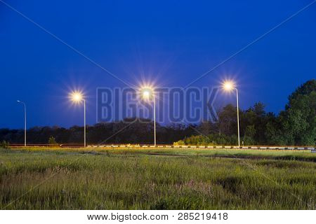 Lights Of Lanterns Near Highway. Night Scene. Grass In A Field At Front Plan. Trees In Woodland Belt