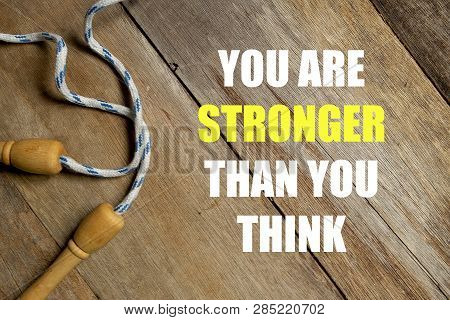 Inspirational motivational quotes You Are Stronger Than You Think on wooden background. Health and fitness concept. poster