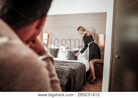 Maid feeling uncomfortable while man watching her working poster