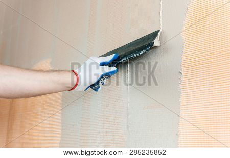 A Worker Is Applying Putty On A Fiberglass Mesh On The Wall. He Is Using A Wide Spatula.