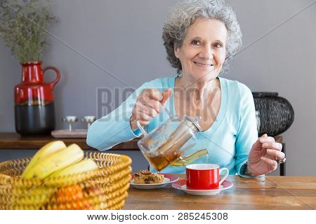 Smiling positive senior woman enjoying teatime. Grey haired lady sitting at table with fruit and dessert and pouring tea for herself. Age concept poster