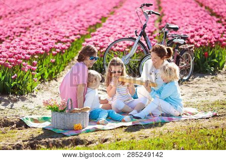 Family Picnic At Tulip Flowers Fields In Holland. Young Mother And Children Eating Lunch In Blooming