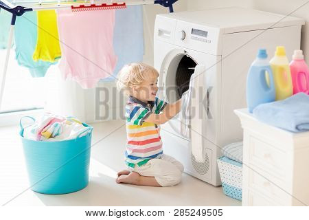 Child in laundry room with washing machine or tumble dryer. Kid helping with family chores. poster
