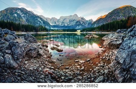 Colorful sunrise on Fusine lake. Picturesque autumn scene with Mangart peak on background. Julian Alps, Udine Province, Italy