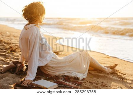 Image of beautiful woman 20s sitting on sand and looking at sea while walking along beach