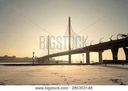 poster of Cable bridge across the Petrovsky fairway at winter sunset in Saint Petersburg, Russia. Part of the Western high-speed diameter.