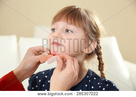 Nurse Applying Medical Patch To Little Girl's Injured Face Indoors. First Aid