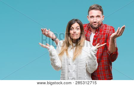 Young couple in love wearing winter sweater over isolated background clueless and confused expression with arms and hands raised. Doubt concept.