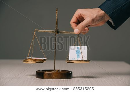 cropped view of businessman with scales of justice and male signs, gender stereotypes concept poster