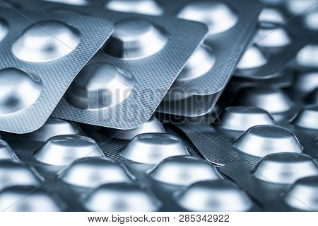 Pile Of Tablets Pill In Blister Packaging To Protect Medicine From Light. Silver Aluminium Foil Blis