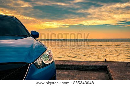 Blue Compact Suv Car With Sport And Modern Design Parked On Concrete Road By The Sea At Sunset In Th