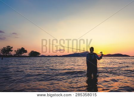 Young Man Fishing On A Lake From The Boat At Sunset.
