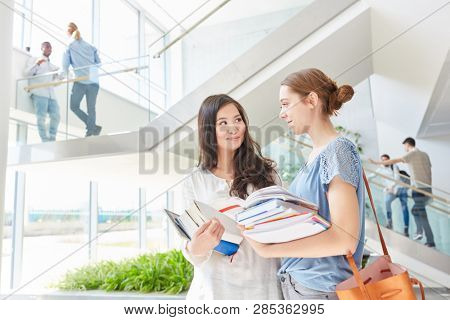 Two young women in school or university together holding books
