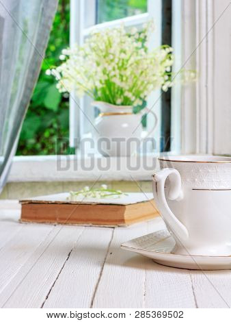 A Cup Of Tea Or Coffee And A Book On A White Wooden Antique Retro Table And A Bouquet Of Lily-of-the