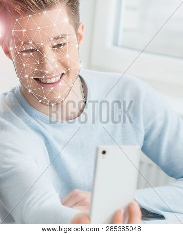 Portrait of a student with an authentication grid on his face. Guy with a smartphone scanning his face. Face id, security, facial recognition, future technology.