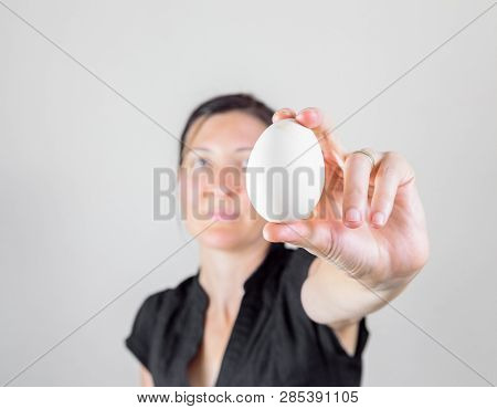 Caucasian Woman With Black Shirt Holding And Showing An Egg Between Her Fingers, Blurry Face On A Wh