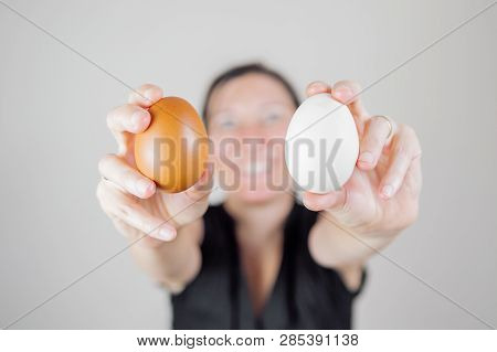 Caucasian Woman With Black Shirt Holding And Showing Two Eggs Between Her Fingers, Blurry Face On A
