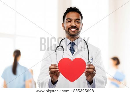 medicine, cardiology and healthcare concept - smiling indian male doctor or cardiologist in white coat with red heart shape and stethoscope over hospital background