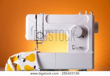 Modern White Electric Sewing Machine With The Fabric On Bright Yellow Background