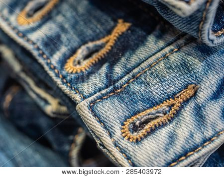 Vibrant Blue Close Up Image Of Waistband Of Denim Jeans With Double Stitching And Metal Tack Buttons