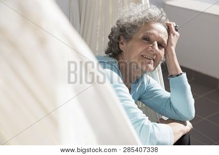 Portrait Of Smiling Senior Woman Sitting In Hammock On Balcony. Happy Retired Woman Posing At Home.