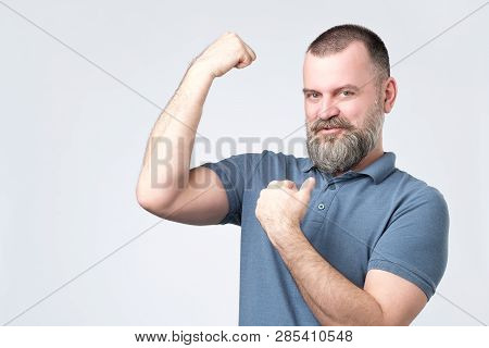 Handsome Middle Age European Bearded Man Over Showing Arm Muscle