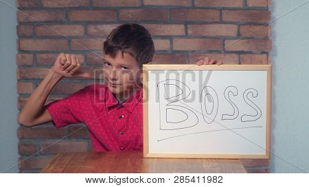 Portrait Little Boy Showing Whiteboard With Handwriting Word Boss. Preadolescent Wearing In Casual R
