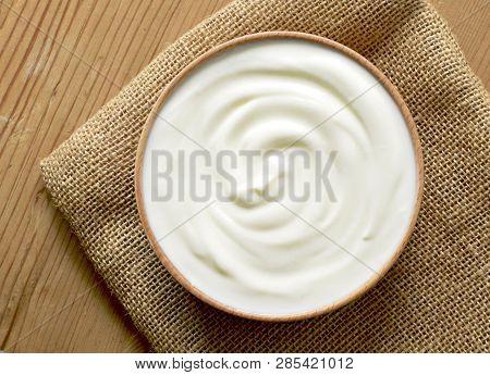 Delicious Yogurt Scene With Wooden Bowl And Sackcloth. Closeup Shot Of Healthy Fresh Yogurt. Top Vie