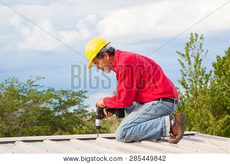 Contractor, builder with yellow hardhat  installing metal panel roof poster