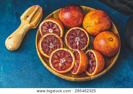 Sliced And Whole Sicilian Blood Oranges Fruits In Wooden Plate And Juicer Over Dark Blue Concrete Ta