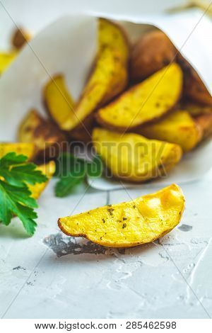 Baked Potato Wedges On Paper With Addition Sea Salt And Parsley On A Light Gray Concrete Background