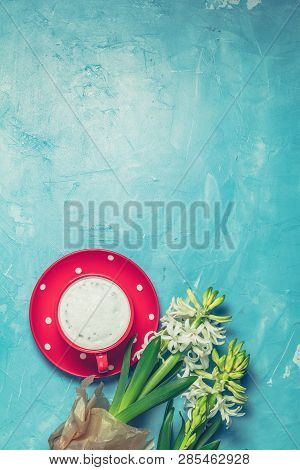 Red In White Dotted Cup Of Coffee With Milk And White Hyacinths On Blue Concrete Surface Background.