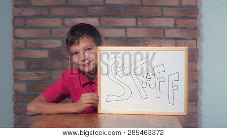 Portrait Little Boy Showing Whiteboard With Handwriting Word Staff. Schoolboy Throw Out Documents. P