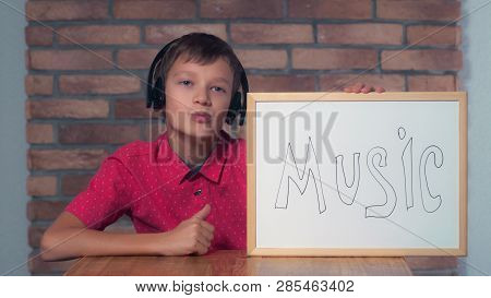 Portrait Little Boy Showing Whiteboard With Handwriting Word Music. Child Listening Music On His Hea