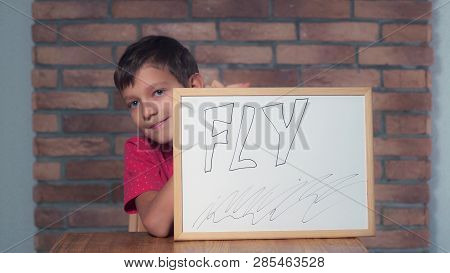 Portrait Little Boy Showing Whiteboard With Handwriting Word Fly. Child Smiling Launch A Paper Airpl