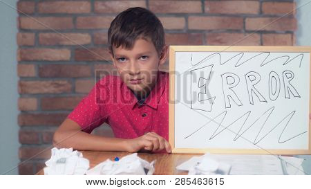 Portrait Little Boy Showing Whiteboard With Handwriting Error. Child Correcting Errors In Documents.