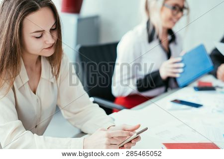 Bored At Work. Team Member Slacking Off. Woman Browsing Smartphone At Workplace.