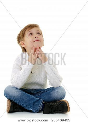 Cute Little Boy Is Sitting On The Floor On A White Background. The Concept Of A Happy Childhood, The