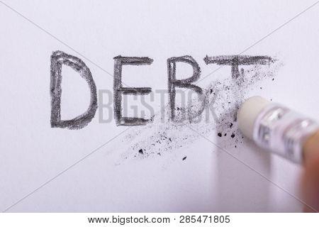 Close-up Of Pencil Eraser Erasing Debt Word On White Paper