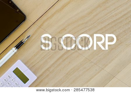 Top View Of Mobile Phone,pen And Calculator On Wooden Background Written With S Corp. Business And F