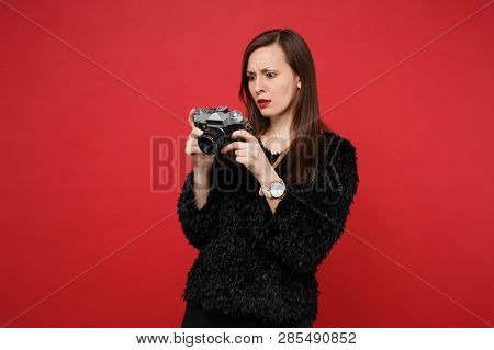 Discouraged Young Woman In Black Fur Sweater Holding, Looking On Retro Vintage Photo Camera Isolated