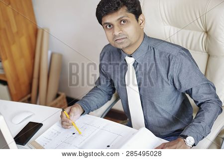 Indian architect working on building blueprint in his bureau poster
